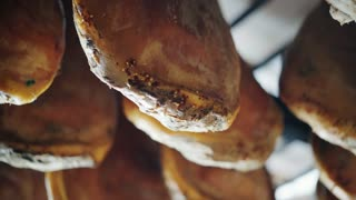 The dried pork thighs hang on the meat market. Prosciutto hanging close up. 4K UHD video 3840x2160. Concept of: tradition, Italy, food, ham.
