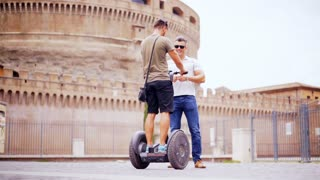The instructor shows the american tourist how to manage and ride on the segway. Eco-friendly transport, modern vehicles.