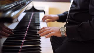 The male play classical piano music on the keyboard instrument Grand Piano at the concert. Close-up of the pianist's hands. 4K (UHD).