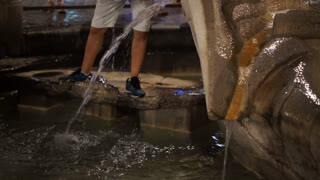 The tourist drinks water and refreshes the ancient Roman fountain, known as Barcaccia, which is located on the square of Piazza di Spagna at night.