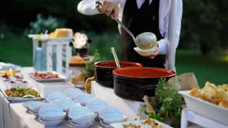 The waiter serves buffet table in hotel or luxury restaurant. Food service worker outdoor. 4K