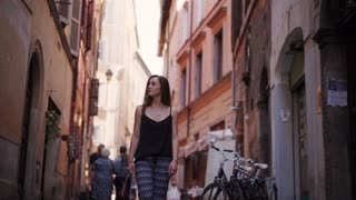 Tourist woman Walking narrow streets of Rome. Girl looking around, exploring sights. Young famale Tourist Visiting Rome.