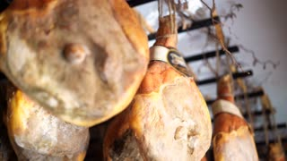 Traditional italian food dried meat - prosciutto in the parma ham factory, hanging, ripening, seasoned. 4K UHD.