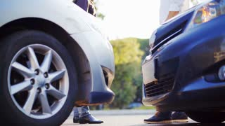 Two drivers shake hands after a small road accident. In the foreground there are two cars. Car insurance. 4K UHD.
