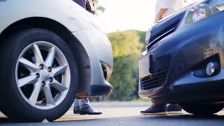 Two drivers shake hands after a small road accident. In the foreground there are two cars. Damaged car. 4K UHD.