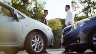 Two man standing by the cars after a collision, inspect the damage and exchange insurance details. Happy ending a small road accident. 4K UHD.
