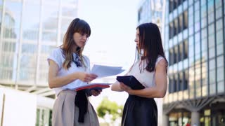 Two young businesswomen chat together as they walk business organization in corporate building.