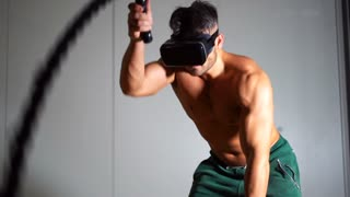 VR sport simulation training at the gym. Strong cheerful man working out with battle ropes in a gym on the head with virtual reality glasses.