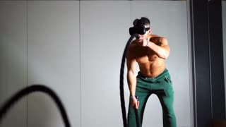 VR sport simulation training sportive man wriggling long heavy ropes working out and training endurance in dark gym on the head with virtual reality glasses. Slow motion 100fps.