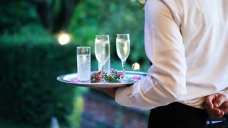 Waiter and champagne glasses on a tray in Luxury Restaurant. Catering service. 4k