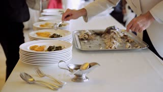 Waiters putting fragrant potatoes with vegetables on the plates with fish and delivering to the guests. Catering company preparing large numbers of food. 4K (UHD).