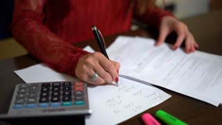 Woman filling tax form, calculating expenses, writing on document. Paperwork in office. Close up.