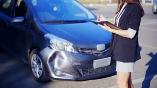 Woman-insurance agent inspects car damage after an accident. Road accident. Car crash. Broken car. 4K UHD.