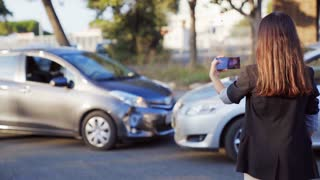 Woman insurance agent taking photo of car accident on mobile phone. A female registers car damage on her smartphone. 4K UHD.