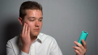 Young man with a remedy against acne for his face. Conception of beauty and body care, creams, skin care.