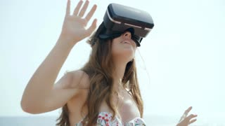 Young woman using virtual reality glasses outdoors in summer time. Slow motion 120fps