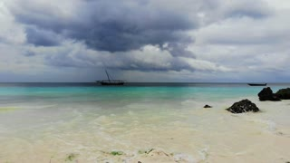 Zanzibar is the tropical island in the ocean. Perfect turquoise water at exotic island. Wooden boat in water of blue lagoon at sunset on cloudy day. Tanzania, Africa, 4k UHD.
