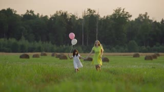 A child running across the field with the girl holding the balloons