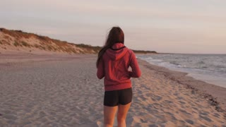 Athlete runs along the sea in the afternoon evening
