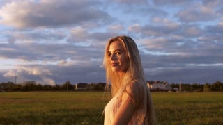 Beautiful girl walking in the field at sunset