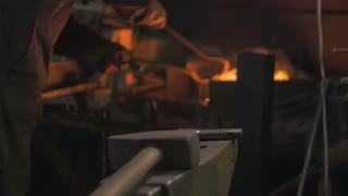 Blacksmith works in his workshop