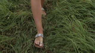 Feet girl goes on a grass