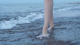 Feet girl stepping on the sea