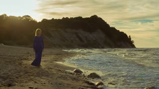 Girl in evening dress is on the seashore