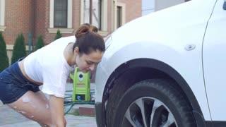 Girl in shorts to wash car