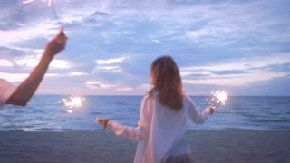 Girls running along the beach with sparklers
