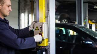 Locksmith lifts cars with a hydraulic lift