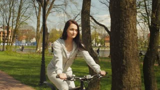 Pretty girl walking on a bicycle