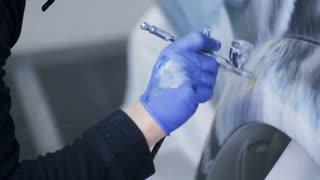 The artist sprays paint on a car body
