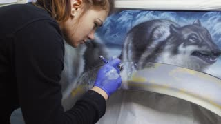 The girl draws a picture on the car body