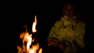 The girl is heated at a fire in the forest at night