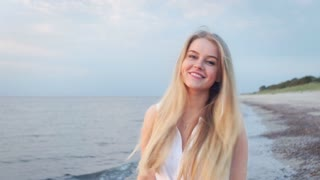The girl is on the beach and smiling