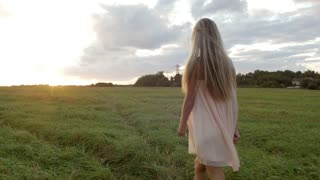 The girl runs across the field at sunset