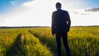 Tired businessman walking in the field