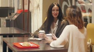 Two girls talking in a coffee shop