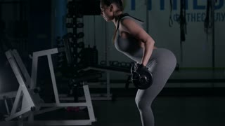 A girl is pulling a bar in the gym