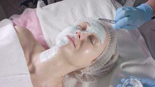 Girl puts cream on face