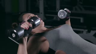 Girl training with dumbbells in the gym