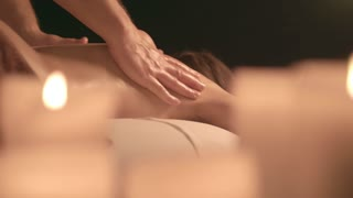 Massage in the spa salon on the background of candles