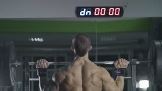 The man lifts the bar above his head