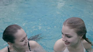 Two girls are swimming on their backs