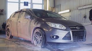 Worker cleans car washing foam