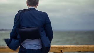 Young man is standing at the pier and his jacket is developed by a strong westray