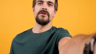 Adult bearded man vlogging with his camera on yellow orange background. Modern lifestyle