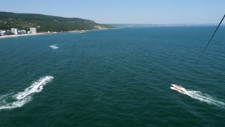 Aerial pov footage of parasailing and parascending over the sea. Active vacation