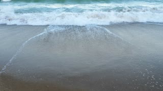 Agitated waves in the sea breaking on the beach